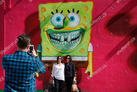 Women pose for a picture in front of a mural by US graffiti artist Ron English in the Wynwood district during Art Basel in Miami, Florida, USA, 06 December 2018. Art galleries and artists from all over the world descend on Miami for the event which is considered one of the world's largest art festivals with art events throughout the city.