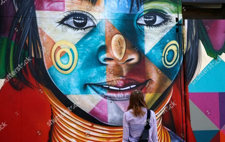 A woman looks at the latest works by Brazilian street artist Eduardo Kobra in the Wynwood district during Art Basel in Miami, Florida, USA, 06 December 2018. Art galleries and artists from all over the world descend on Miami for the event which is considered one of the world's largest art festivals with art events throughout the city.