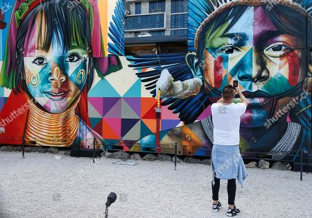 A man takes a photo of the latest works by Brazilian street artist Eduardo Kobra in the Wynwood district during Art Basel in Miami, Florida, USA, 06 December 2018. Art galleries and artists from all over the world descend on Miami for the event which is considered one of the world's largest art festivals with art events throughout the city.