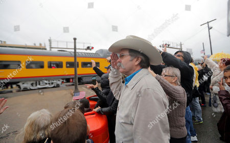 Dennis Ivy from Huntsville, Texas, left, salutes as people pay their respects as the train carrying the casket of former President George H.W. Bush passes through Navasota, Texas