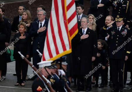 George W. Bush, Jeb Bush. Former Florida Gov. Jeb Bush, left of flag, and former President George W. Bush, right of flag, watch as the flag-draped casket of former President George H.W. Bush is carried by a joint services military honor guard after if arrived by train, in College Station