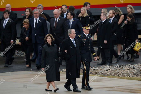 George W.Bush, Laura Bush. Former President George W. Bush and wife Laura are escorted as other family member follow after the flag-draped casket of former President George H.W. Bush arrived by train, in College Station