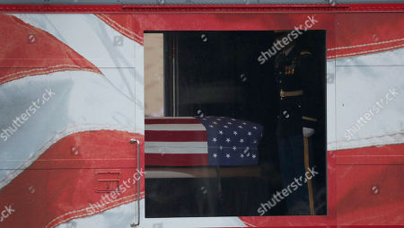 The flag-draped casket of President George H. W. Bush arrives by train to Texas A&M University for burial at the George Bush Presidential Library, in College Station