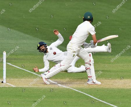 Lokesh Rahul (L) of India dives for a ball from Patrick Cummins (R) of Australia during day two of the first Test match between Australia and India at the Adelaide Oval in Adelaide, Australia, 06 December 2018.