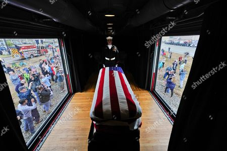 The flag-draped casket of former President George H.W. Bush passes through Magnolia, Texas, along the route from Spring to College Station, Texas
