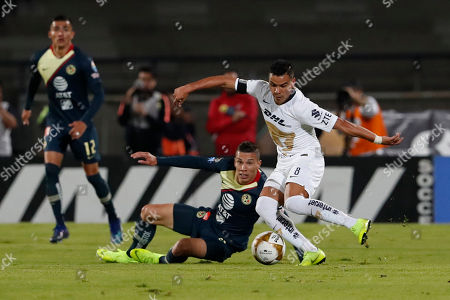 Pumas' Pablo Barrera, front, kicks the ball during a Mexico soccer league first leg semifinals match against America in Mexico City