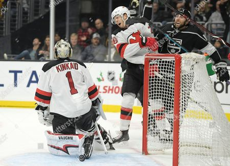 Stock Photo of Damon Severson, Michael Amadio, Keith Kinkaid. New Jersey Devils defenseman Damon Severson, center, is hit on the face by the stick of Los Angeles Kings center Michael Amadio, right, after goaltender Keith Kinkaid, left, gave up a goal to Kyle Clifford during the second period of an NHL hockey game, in Los Angeles