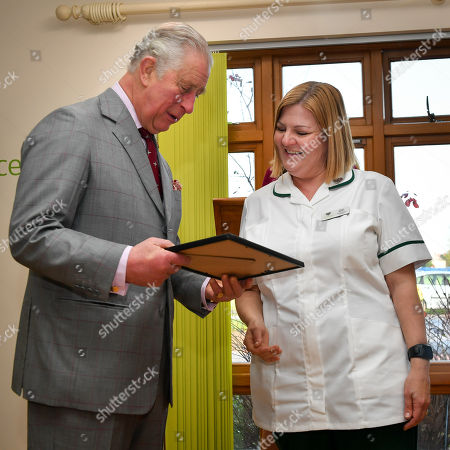 Stock Image of Prince Charles, in his role as Patron, presents a certificate to Occupational Therapist Rachel Roberts during his visit to the City Hospice, located in Whitchurch Hospital Grounds, Whitchurch, Cardiff.