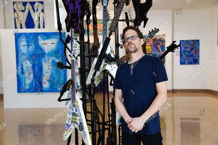 Former Metallica Bassist Jason Newsted poses in from of his artwork during his Solo Art Show at Sagamore Hotel