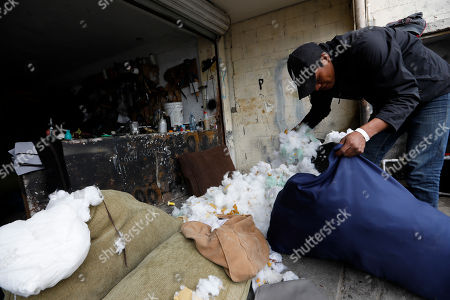 Honduran migrant Jose Perez, 22, stuffs a pillow as he works as a day laborer at an upholstery shop in Tijuana, Mexico. Mexican authorities have encouraged all of the migrants to regularize their status in Mexico and seek work