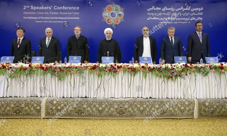 Stock Photo of Hassan Rouhani, Chen Zhu, Binali Yildirim, Vyacheslav Volodin, Ali Larijani, Asad Qaiser, Abdul Rauf Ibrahimi. From left to right, deputy chairman of the National People's Congress of China Chen Zhu, Turkey's speaker of parliament Binali Yildirim, Iran's parliament speaker Ali Larijani, Iran's President Hassan Rouhani, speaker of the national assembly of Pakistan Asad Qaiser, Russian parliament speaker Vyacheslav Volodin, and Afghan parliament speaker Abdul Rauf Ibrahimi, listen to the Iranian national anthem at the start of their meeting on fighting terrorism in Tehran, Iran, . President Hassan Rouhani on Saturday warned Western countries that they will face a massive influx of drugs if Iran becomes weakened by U.S. sanctions. The man on the left is unidentified