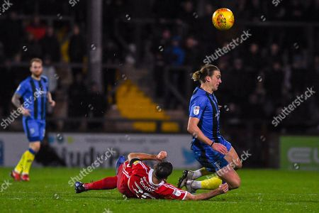 Tom Eaves of Gillingham (9) is tackled by Charlie Goode of Scunthorpe United (20) during the EFL Sky Bet League 1 match between Scunthorpe United and Gillingham at Glanford Park, Scunthorpe