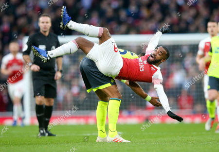 Alexandre Lacazette of Arsenal takes a tumble over the back of Mathias Zanka Jorgensen of Huddersfield Town