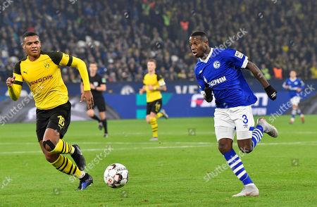 Schalke's Hamza Mendyl and Dortmund's Manuel Akanji, left, challenge for the ball during the German Bundesliga soccer match between FC Schalke 04 and Borussia Dortmund at the Arena in Gelsenkirchen, Germany