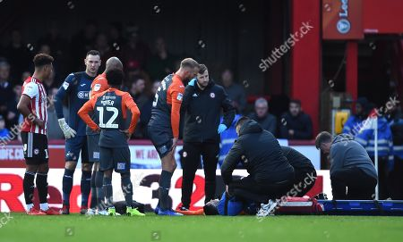 Stock Image of Martin Olsson of Swansea City is treated before being stretchered from the field.