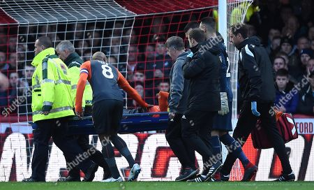 Martin Olsson of Swansea City is treated before being stretchered from the field.