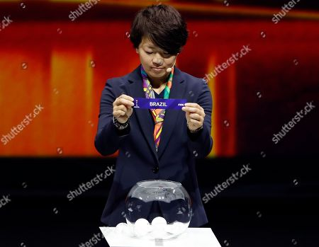 Aya Miyama holds up the team name of Brazil during the women's soccer World Cup France 2019 draw, in Boulogne-Billancourt, outside Paris