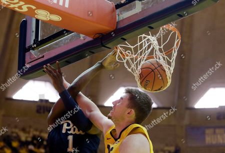 Pittsburgh guard Xavier Johnson (1) dunks over West Virginia forward Logan Routt (31) during the first half of an NCAA college basketball game, in Morgantown, W.Va