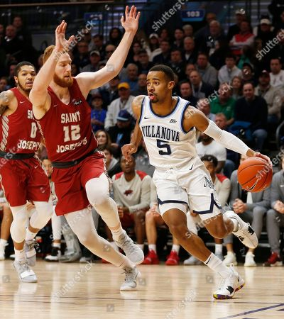 Villanova guard Phil Booth (5) dribbles around Saint Joseph's forward Anthony Longpre (12) during the first half of an NCAA college basketball game, in Villanova, Pa