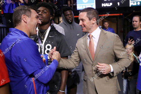 Players names here. Florida head coach Mike White, right, shakes hands with Florida head football coach Dan Mullen before the first half of an NCAA college basketball game, in Gainesville, Fla. Michigan State defeated Florida 63-59