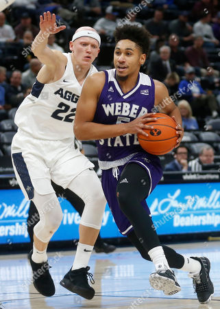 Cody John, Brock Miller. Weber State guard Cody John (5) drives to the basket as Utah State guard Brock Miller (22) defends in the first half during an NCAA college basketball game, in Salt Lake City