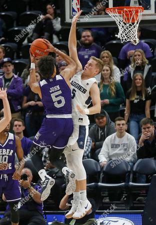 Cody John, Sam Merrill. Weber State guard Cody John (5) shoots as Utah State guard Sam Merrill (5) defends in the second half of an NCAA college basketball game, in Salt Lake City