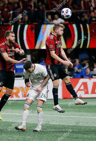 Atlanta United defender Julian Gressel (24) heads the ball against Portland Timbers defender Liam Ridgewell (24) during the second half of the MLS Cup championship soccer game, in Atlanta. Atlanta won 2-0