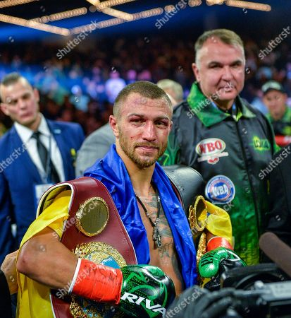 Vasyl Lomachenko poses with the belts after defeating Jose Pedraza in the WBO title lightweight boxing match at Madison Square Garden, in New York