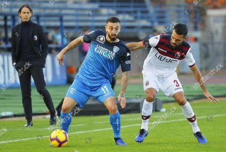 Empoli's forward Francesco Caputo (L) and Bologna's defender Giancarlo Gonzalez in action during the Italian Serie A soccer match Empoli vs Bologna at Carlo Castellani stadium in Empoli, Italy, 09 December 2018.