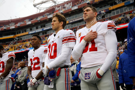 Stock Photo of New York Giants quarterback Eli Manning, center, stands on the field with teammates Wayne Gallman, left, and Zak DeOssie during a rendition of the national anthem before an NFL football game against the Washington Redskins, in Landover, Md