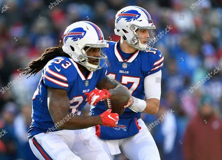 Buffalo Bills quarterback Josh Allen, rear, fakes a handoff to running back Chris Ivory (33) during the first half of an NFL football game against the New York Jets, in Orchard Park, N.Y
