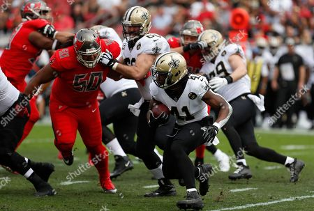 New Orleans Saints running back Alvin Kamara (41) runs as center Max Unger (60) blocks Tampa Bay Buccaneers defensive tackle Vita Vea (50) during the first half of an NFL football game, in Tampa, Fla