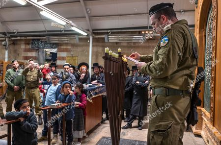 Stock Picture of Jewish settler children watch along with some soldier and ultra-Orthodox Jews as an Israeli army officer lights the Hanukkah candles on the final day of the Jewish holiday inside the Tomb of the Patriarchs in the West Bank city of Hebron, 09 December 2018. The cave is also holy site to Muslims and is the second most holy site to Jews, after the Western Wall, as it is the burial site of Abraham and Sarah, Isaac and Rebecca, Jacob and Leah. Hanukkah, also known as the 'Festival of Lights', is one of the most important Jewish holidays and is celebrated by Jews worldwide.
