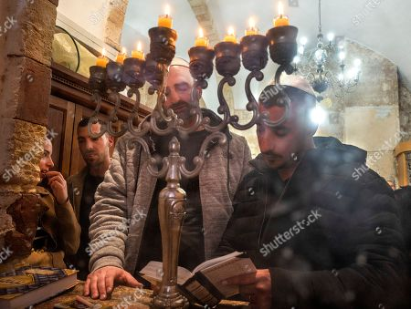 Jewish settlers pray in front of the eight candles lit on a Hanukkah candelabra on the final day of the Jewish holiday of Hanukkah inside the Tomb of the Patriarchs in the West Bank city of Hebron, 09 December 2018. The cave is also holy site to Muslims and is the second most holy site to Jews, after the Western Wall, as it is the burial site of Abraham and Sarah, Isaac and Rebecca, Jacob and Leah. Hanukkah, also known as the 'Festival of Lights', is one of the most important Jewish holidays and is celebrated by Jews worldwide.