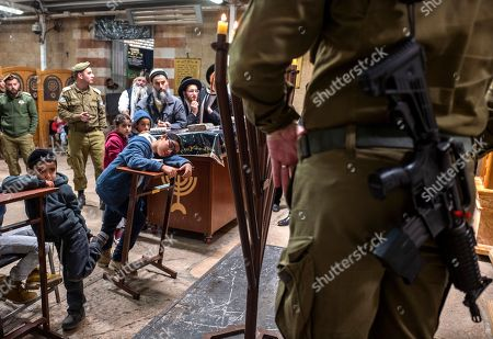 Stock Photo of Jewish settler children watch along with some soldier and ultra-Orthodox Jews as an Israeli army officer lights the Hanukkah candles on the final day of the Jewish holiday inside the Tomb of the Patriarchs in the West Bank city of Hebron, 09 December 2018. The cave is also holy site to Muslims and is the second most holy site to Jews, after the Western Wall, as it is the burial site of Abraham and Sarah, Isaac and Rebecca, Jacob and Leah. Hanukkah, also known as the 'Festival of Lights', is one of the most important Jewish holidays and is celebrated by Jews worldwide.