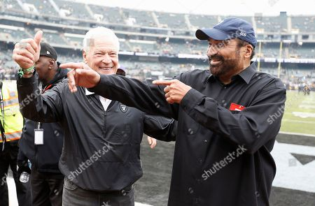 Former Oakland Raiders linebacker Phil Villapiano, left, and with former Pittsburgh Steelers running back Franco Harris gesture toward fans before an NFL football game between the Raiders and the Steelers in Oakland, Calif
