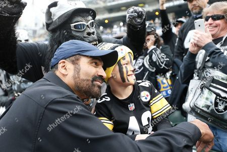 Former Pittsburgh Steelers running back Franco Harris poses with fans before an NFL football game between the Oakland Raiders and the Steelers in Oakland, Calif