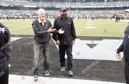 Former Oakland Raiders linebacker Phil Villapiano, left, walks with former Pittsburgh Steelers running back Franco Harris before an NFL football game between the Raiders and the Steelers in Oakland, Calif