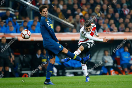 Juan Quintero of Argentina's River Plate, left, strikes the ball pressures by Fernando Gago of Argentina's Boca Juniors during extra time of the Copa Libertadores final soccer match at the Santiago Bernabeu stadium in Madrid, Spain