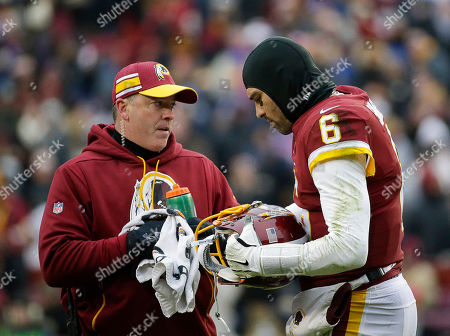 Washington Redskins QB #6 Mark Sanchez adjusts his helmet with the help of the equipment staff during a NFL football game between the Washington Redskins and the New York Giants at FedEx Field in Landover, MD