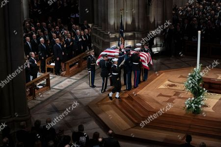 The flag-draped casket of former President George H.W. Bush is carried by a military honor guard past former President George W. Bush and wife Laura Bush, President Donald Trump, first lady Melania Trump, former President Barack Obama, Michelle Obama, former President Bill Clinton, former Secretary of State Hillary Clinton, former President Jimmy Carter, and Rosalynn Carter during a State Funeral at the National Cathedral, in Washington