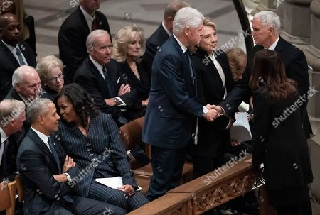Stock Photo of Former President Bill Clinton, and former Secretary of State Hillary Clinton, and Vice President Mike Pence and Karen Pence greet each other, at right, before a State Funeral for former President George H.W. Bush at the National Cathedral, in Washington. Also seen in the first row, at left, are former President Barack Obama and Michelle Obama. In the second row, form left, are former Vice President Dan Quayle, former Vice President Dick Cheney and his wife Lynn Cheney, former Vice President Joe Biden and his wife Jill Biden