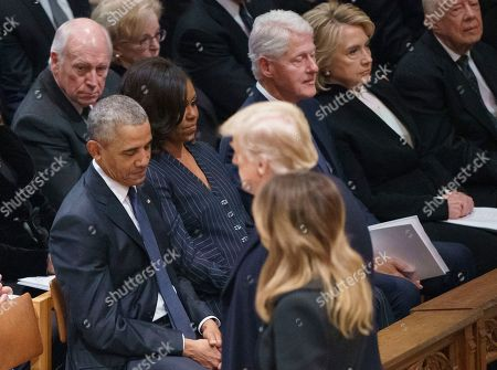 Former President Barack Obama, Michelle Obama, former President Bill Clinton, former Secretary of State Hillary Clinton, and former sit together as President Donald Trump and first lady Melania Trump arrive for the start of the State Funeral of former President George H.W. Bush at the National Cathedral, in Washington. In the second row, form left, are former Vice President Dick Cheney and Lynn Cheney