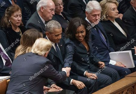 President Donald Trump, left, reaches over first lady Melania Trump and Former President Barack Obama, to shake hands with Michelle Obama, as former President Bill Clinton, former Secretary of State Hillary Clinton, sit right, before the start of the State Funeral of former President George H.W. Bush at the National Cathedral, in Washington. In the second row, form left, are Marilyn Quayle, former Vice President Dick Cheney, and Lynn Cheney