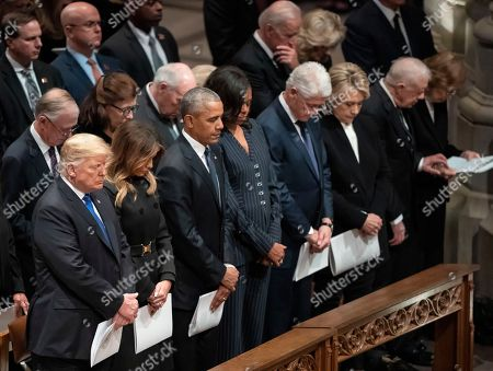 President Donald Trump, Melania Trump, former President Barack Obama, Michelle Obama, former President Bill Clinton, and former Secretary of State Hillary Clinton, former President Jimmy Carter, and Rosalynn Carter, bow their heads during the State Funeral of former President George H.W. Bush at the National Cathedral, in Washington. In the second row are former Vice President Dan Quayle, and his wife Marilyn Quayle and former Vice President Dick Cheney, former President Joe Biden and Jill Biden