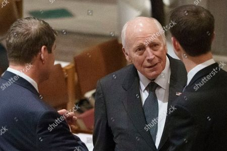 Former Vice President Dick Cheney talks with other mourners before a State Funeral for former President George H.W. Bush at Washington National Cathedral in Washington