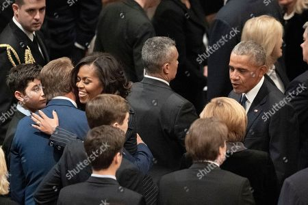Michelle Obama hugs Sen. Jeff Flake, R-Ariz., left, and she and former President Barack Obama, left, mingle before a State Funeral for former President George H.W. Bush at Washington National Cathedral in Washington