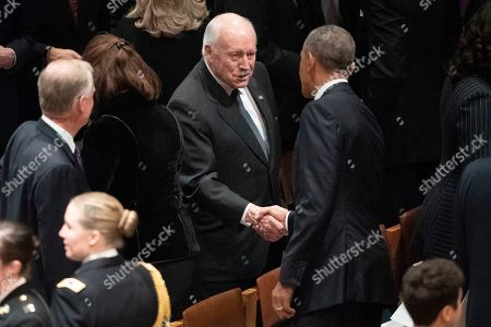 Former President Barack Obama, and former Vice President Dick Cheney shake hands before a State Funeral for former President George H.W. Bush at Washington National Cathedral in Washington
