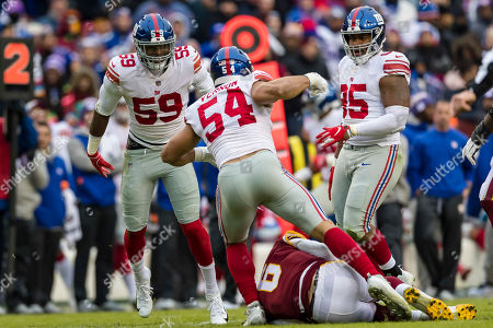 Washington Redskins quarterback Mark Sanchez (6) is sacked by New York Giants linebacker Olivier Vernon (54) and linebacker Lorenzo Carter (59) during the first half of the NFL game between the New York Giants and the Washington Redskins at FedExField in Landover, Maryland
