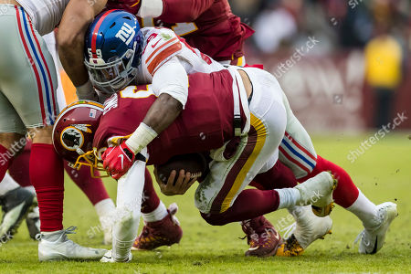 Washington Redskins quarterback Mark Sanchez (6) is sacked by New York Giants linebacker Lorenzo Carter (59) during the second half of the NFL game between the New York Giants and the Washington Redskins at FedExField in Landover, Maryland